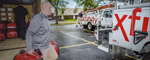 Male Xfinity employee carrying canisters of gas to xfinity trucks during Hurricane Harvey